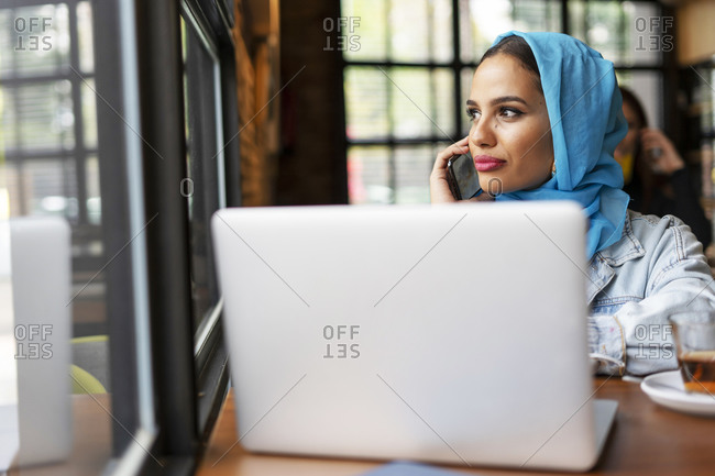 Businesswoman wearing turquoise hijab in a cafe and working