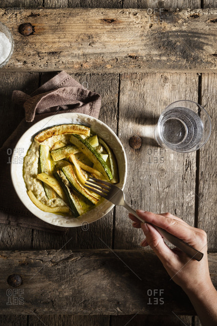 Cropped hand of woman eating hummus with fried zucchini on wooden table