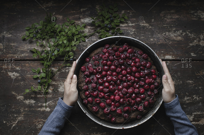 Cropped hands of boy holding cherry brownie pie on wooden table