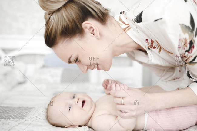 Mother with her cute smiling baby girl in the bedroom