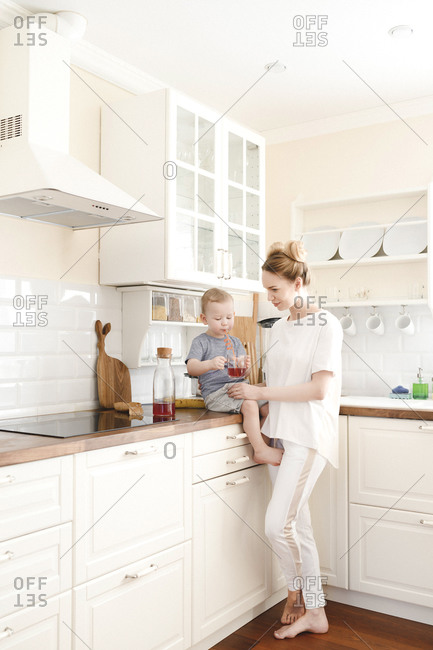 Mother with her little boy drinking a juice in the kitchen