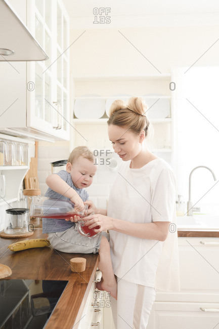 Mother with her little boy with juice in the kitchen