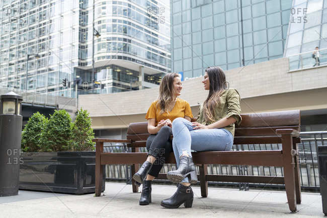 Happy lesbian couple sitting on a bench in the city- London- UK