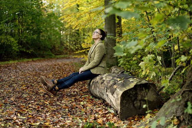 Mature woman sitting on a tree trunk in a autumn forest
