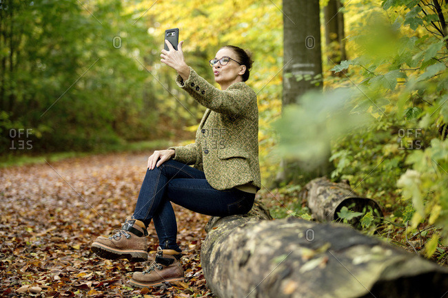 Mature woman taking a selfie in a autumn forest