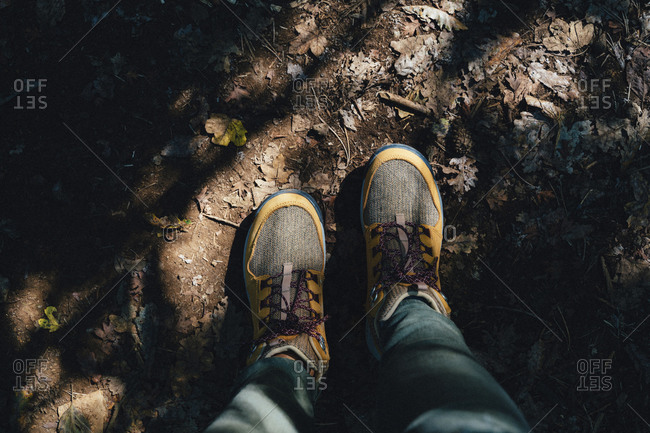 Hiking boots in autumn on a path with leaves