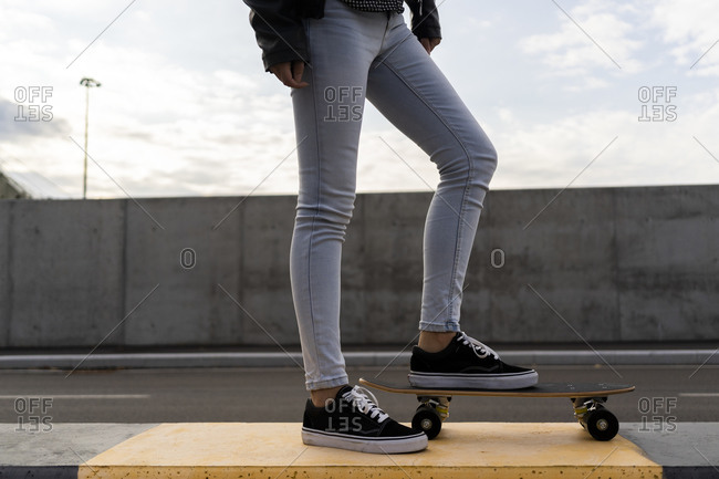 Legs of woman with skateboard standing on bollard