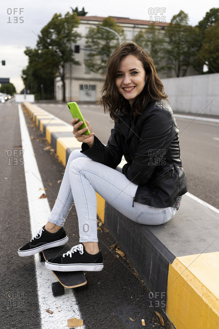 Portrait of smiling young woman with skateboard sitting on bollard using smartphone