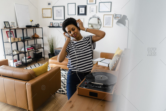Happy young woman listening to music with headphones and record player at home