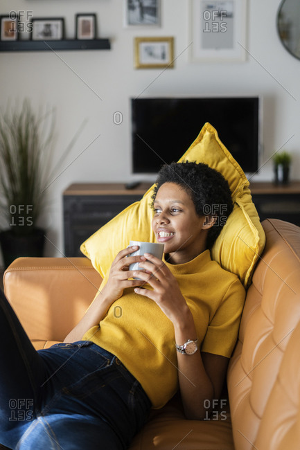 Relaxed young woman lying on couch at home holding mug
