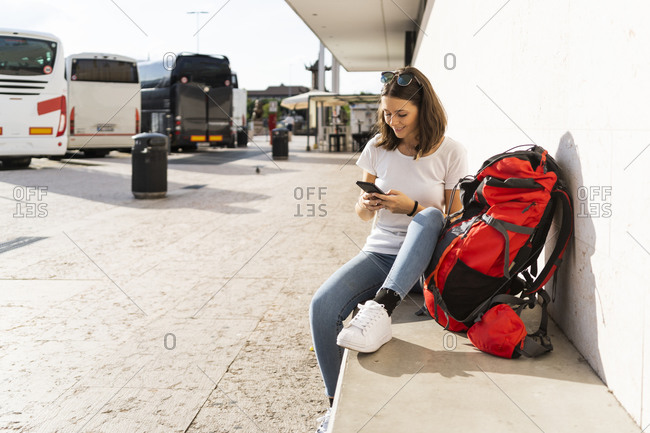 Young female backpacker with red backpack using smartphone- Verona- Italy