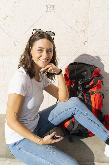Young female backpacker with red backpack holding smartphone