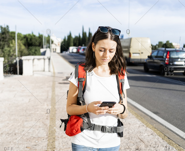 Young female backpacker with red backpack using smartphone in the city- Verona- Italy