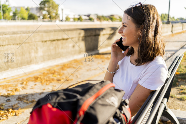 Young female backpacker with red backpack using smartphone- sitting on a benach in Verona- Italy