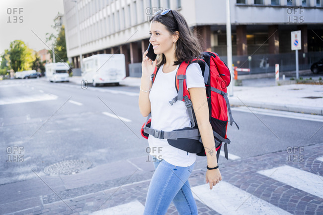 Young female backpacker using smartphone in the city- Verona- Italy