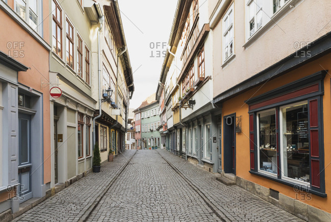 March 17, 2019: Diminishing perspective of empty cobble street amidst residential buildings in Erfurt- Germany