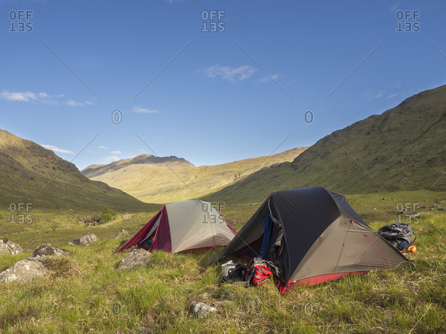 Tents on grassy land against blue sky during sunny day- Scotland- UK