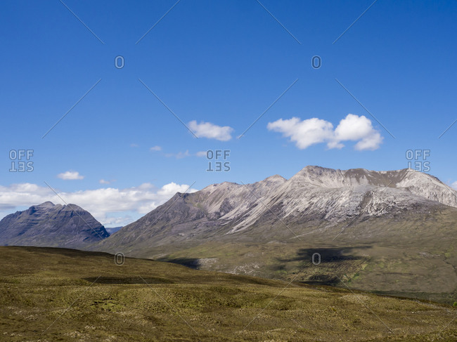 Scenic view of mountains against blue sky during sunny day- Scotland- UK