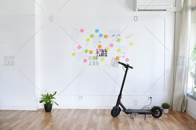 Electric scooter in front of a wall full of sticky notes in a bright modern office