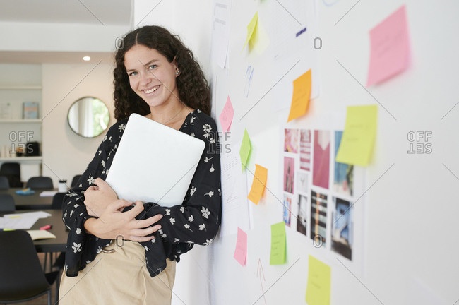 Portrait of smiling young businesswoman leaning against a wall full of sticky notes in an office