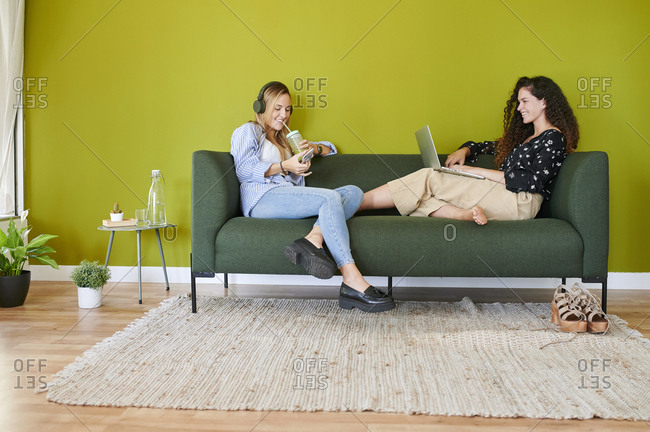 Two smiling young businesswomen sitting on couch in modern office