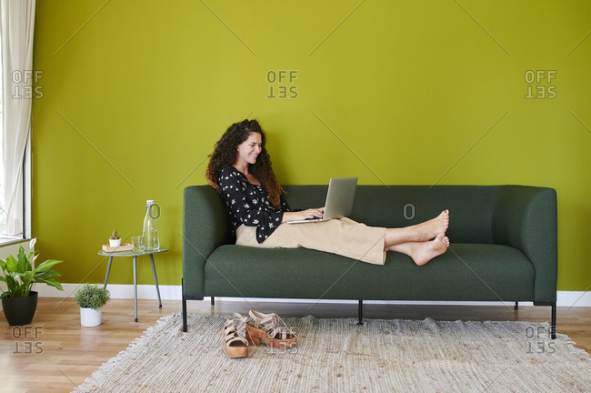 Smiling young businesswoman using laptop on couch in modern office