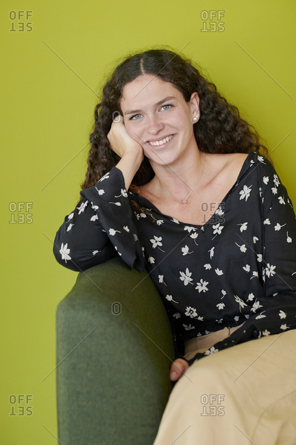 Portrait of smiling young woman sitting on green couch