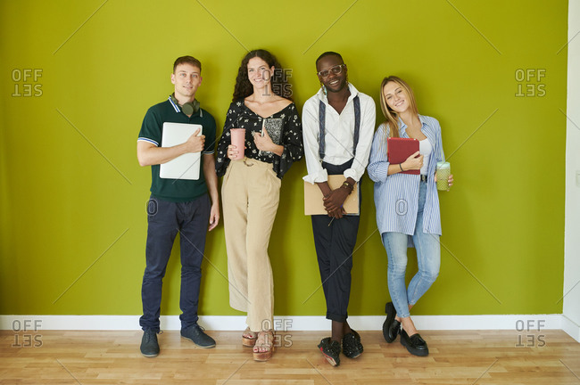 Portrait of smiling casual colleagues standing together in front of a green wall in a modern office