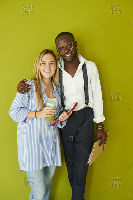 Portrait of smiling casual business couple standing together in front of a green wall