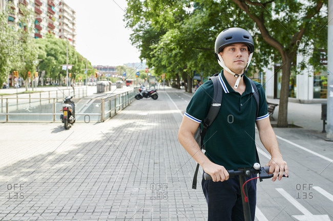 Casual young businessman riding e-scooter on bicycle lane in the city