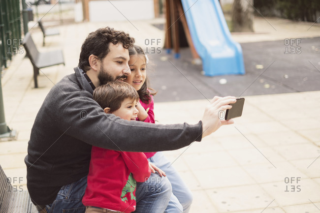 Father taking selfie with his daughter and son on playground