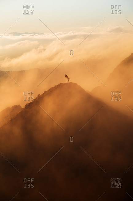 Hiker on top of a mountain doing a backflip during an epic sunrise with fog