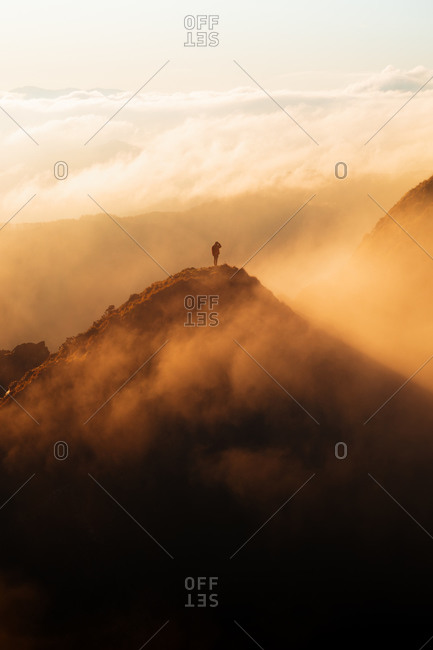 Hiker on top of a mountain during an epic sunrise with fog