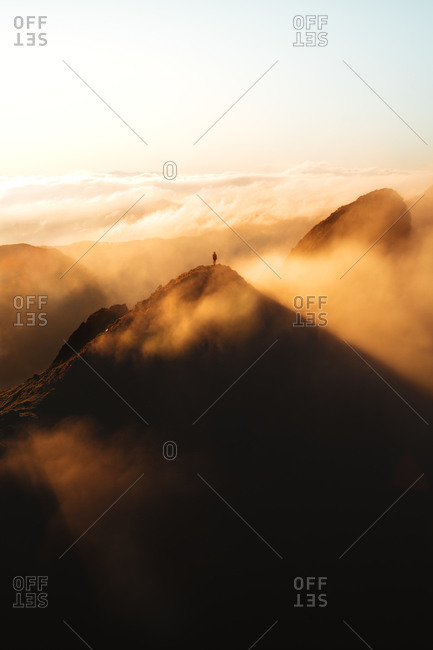 Hiker on top of a mountain peak during an epic sunrise with fog