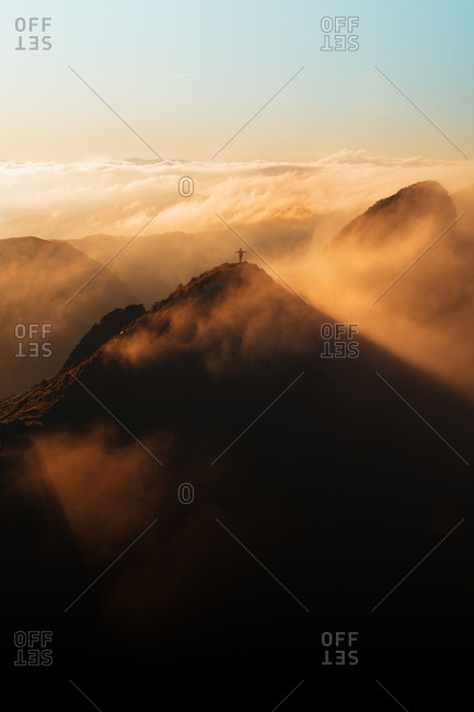 Hiker on top of a mountain with arms spread during an epic sunrise with fog