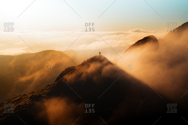Hiker on top of a mountain during an epic golden sunrise with fog