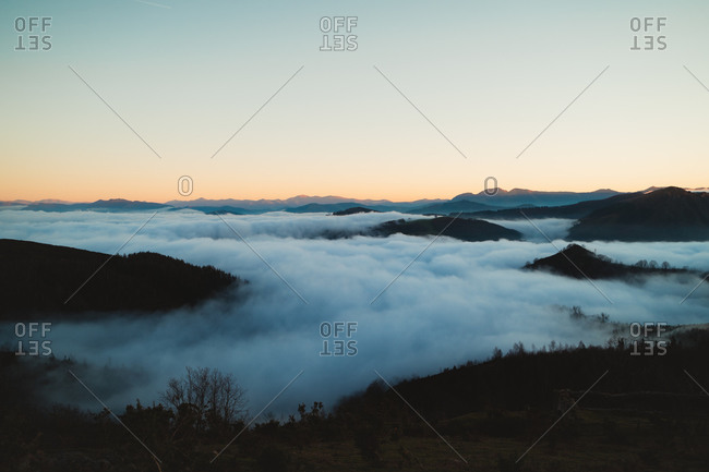 Sea of clouds in Basque Country, Spain below the mountains during sunset