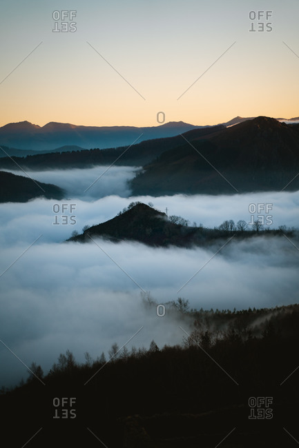 View over a sea of clouds in Basque Country, Spain below the mountains during sunset