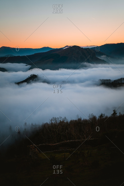 Sea of clouds below the mountains during sunset in Basque Country, Spain