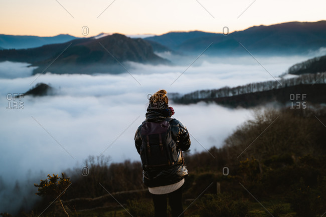 Young woman watching the clouds below the mountains from the top of a hill in Basque Country