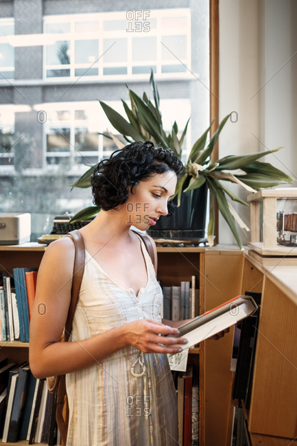 Young woman reading a book in a library