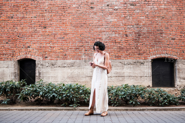 Young woman texting on cell phone outside of an old brick building