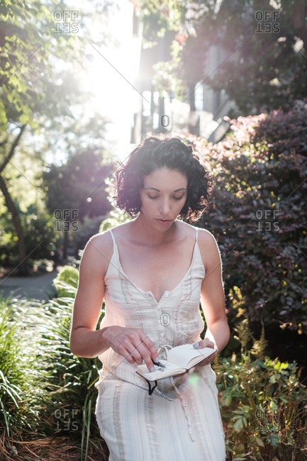 Young woman sitting in garden with small sketch book
