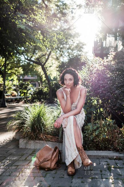 Beautiful young woman sitting in a city garden