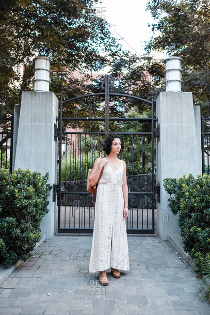 Young woman standing by gate at a city garden