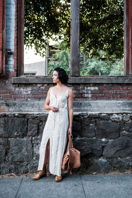 Beautiful young woman in summer dress standing by old brick and stone building