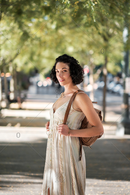 Portrait of a young woman with curly short hair standing on city sidewalk