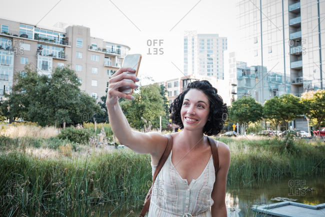 Young woman taking selfie in a city park