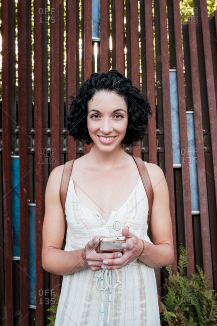 Portrait of a young woman with curly short hair by wooden structure with cell phone