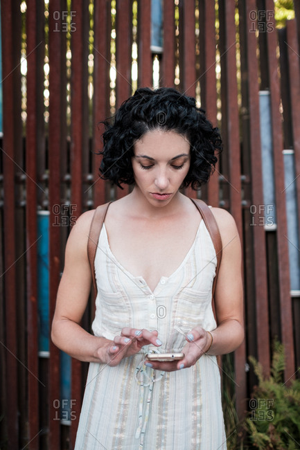 Young woman with curly short hair by wooden structure with cell phone